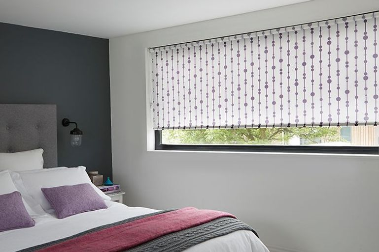 purple striped pattern roller blinds in a bedroom window
