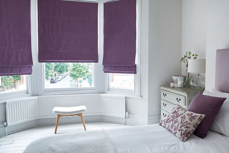 purple blackout roman blinds in a large living room bay window