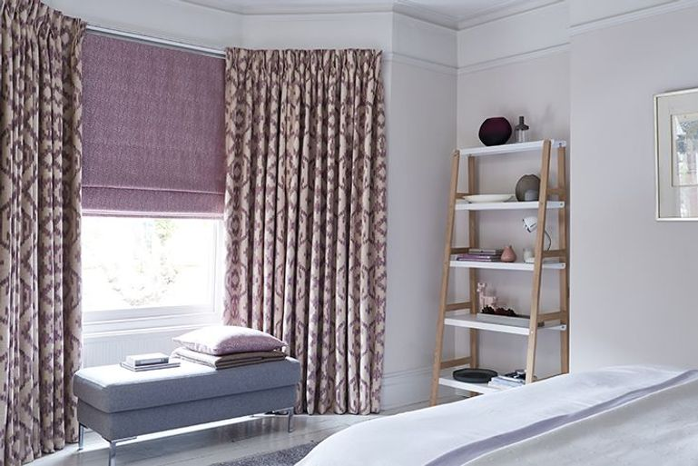 purple and gold full length curtains with purple blackout roman blinds in a living room window