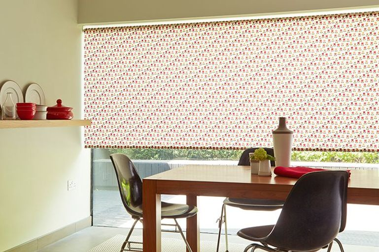 nelda red patterned roller blinds in a kitchen with large patio windows and a dining room table