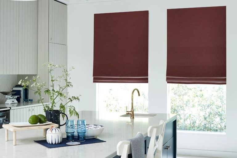red blackout roman blinds in a kitchen window