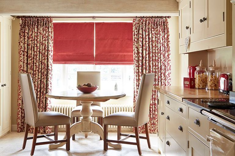 bright red blackout roman blinds with flowery pattern red and cream curtains in a dining room window