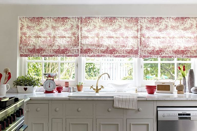 cherry swirl pattern on cream roman blinds in a kitchen window