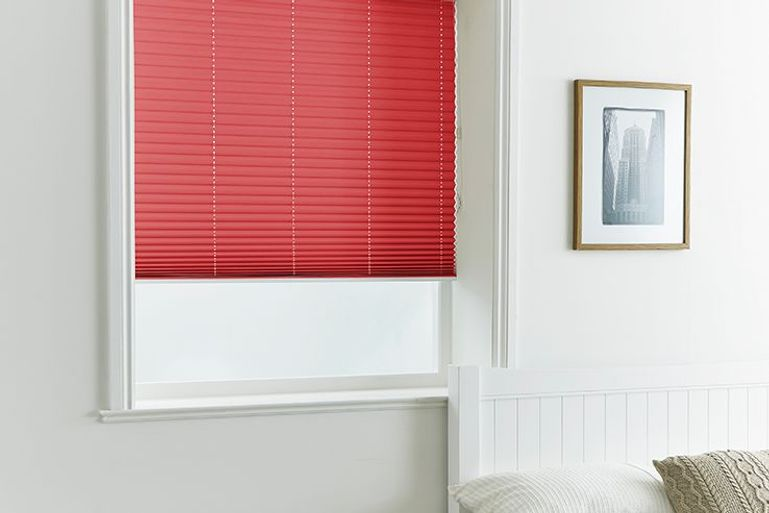 plain white bedroom decor with statement red pleated blinds