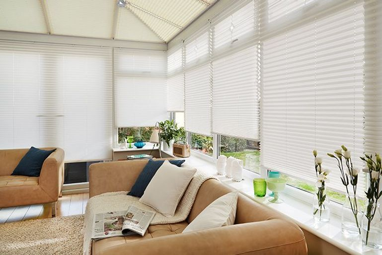 white pleated blinds in a conservatory window with large brown leather sofas