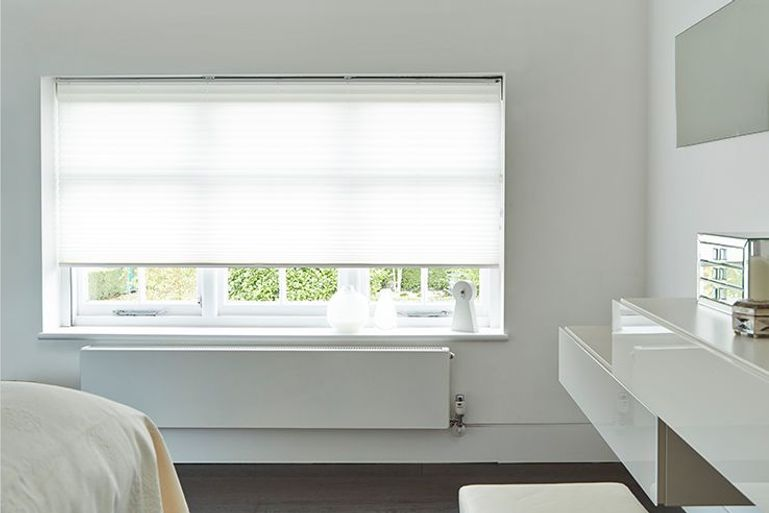 white bedroom with white pleated blinds in the window