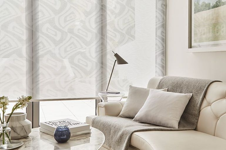 geometric pattern roller blinds in ice white and grey hanging in a living room window