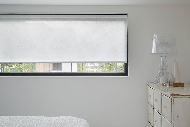 plain white roller blinds in a bedroom window