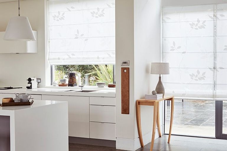 white roman blinds in a kitchen with large patio doors