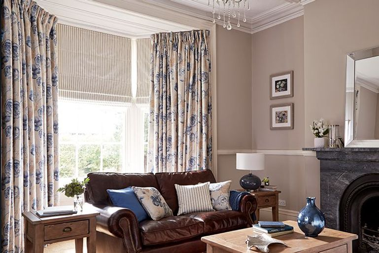 Cream and blue roman blinds in a living room with curtains and a brown leather sofa