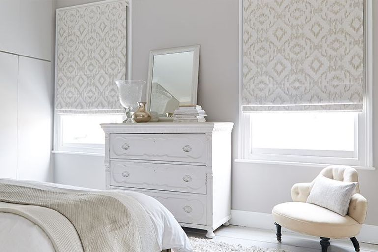 cream patterned roman blinds in a bedroom with 2 windows