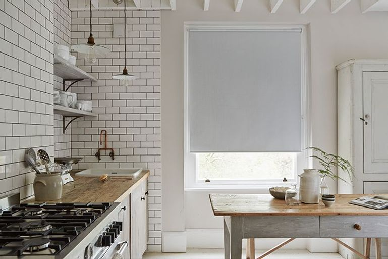 white blackout roller blinds in a kitchen window