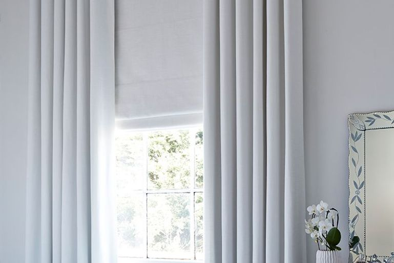 white roller blinds and white blackout curtains in a window