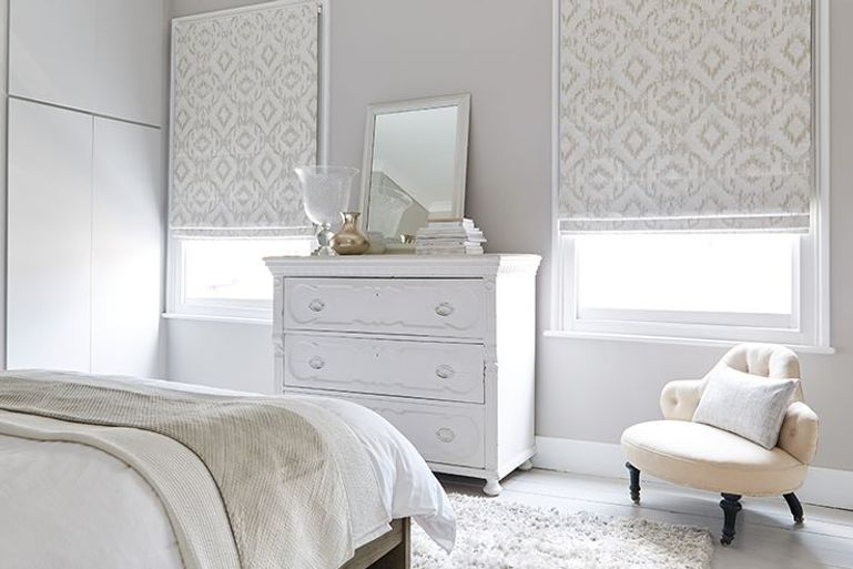 white roller blinds in blackout fabric with cream details in a bedroom window