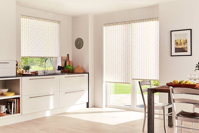 white roller blinds with striped yellow detail in a kitchen window