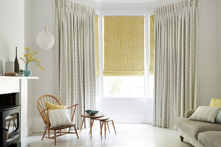 yellow roman blinds with patterned curtains in a modern living room