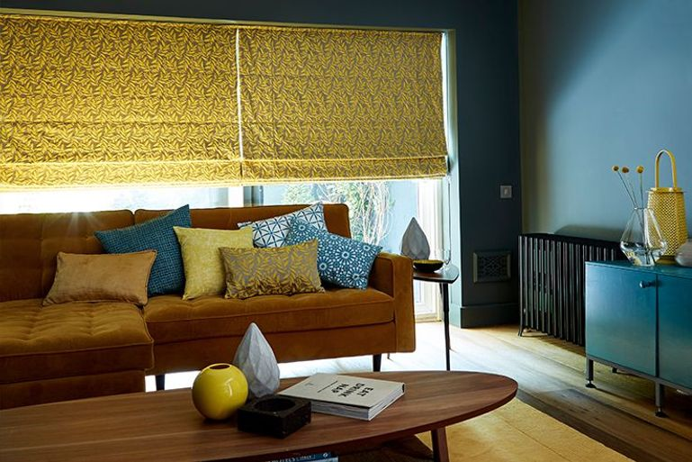 deep yellow roman blinds in a dark blue living room