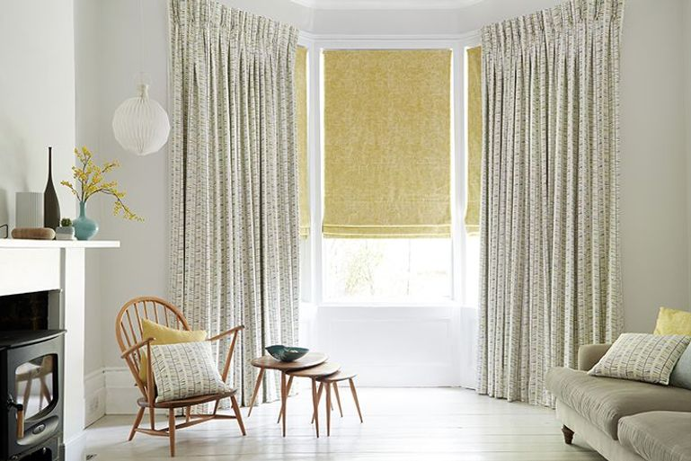 yellow blackout roman blinds paired with full length curtains in a modern living room