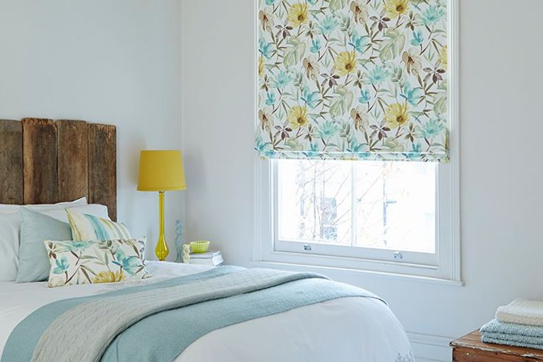 colourful blue and white blackout blinds with yellow flower details in a bedroom window