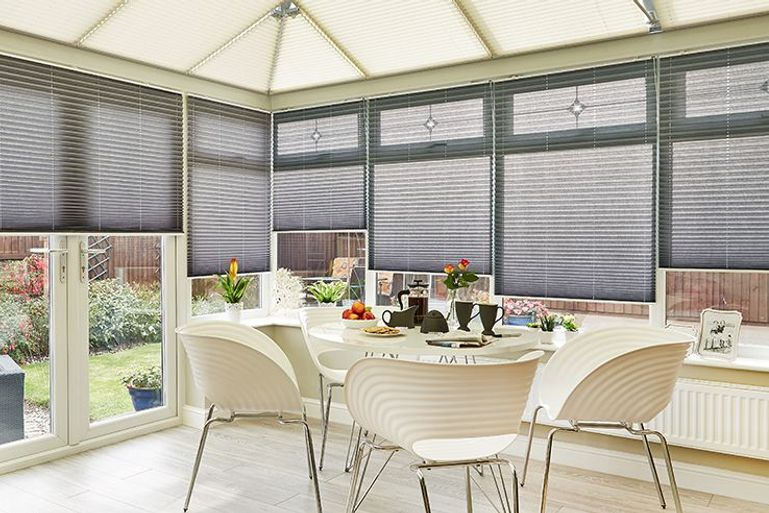 modern conservatory with dining table and silver pleated blinds at the windows