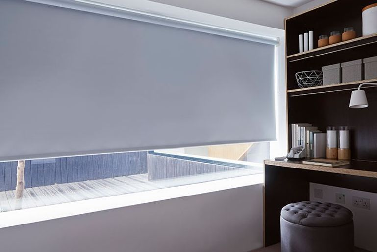 light silver roller blind in a home office window