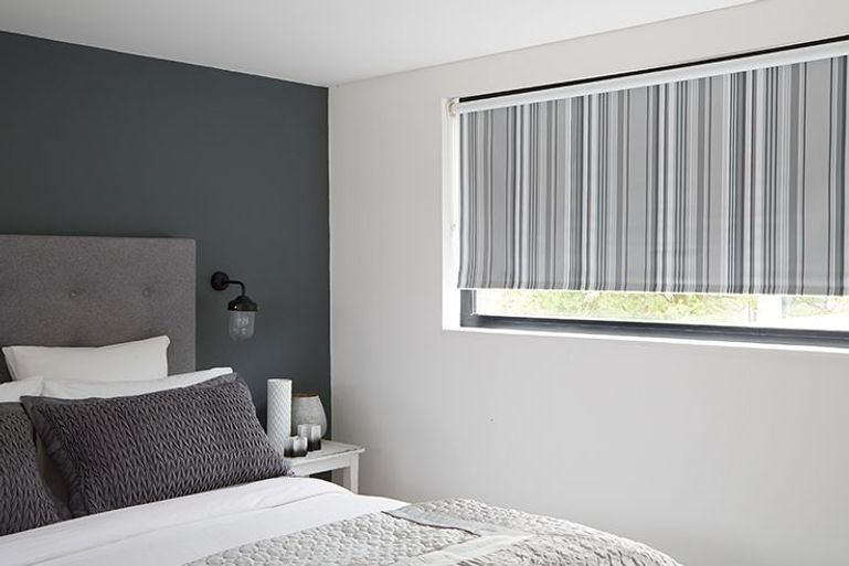 vertical striped roller blind in black and silver in a bedroom window