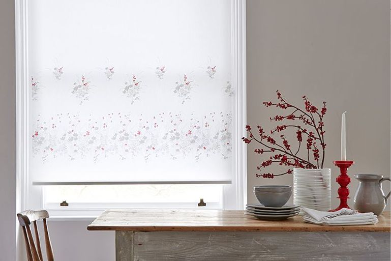 white roller blinds with red and silver flower pattern in a dining room window