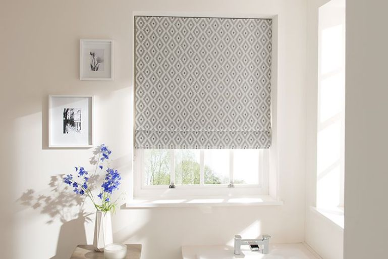 silvery grey patterned roman blinds in a bathroom window