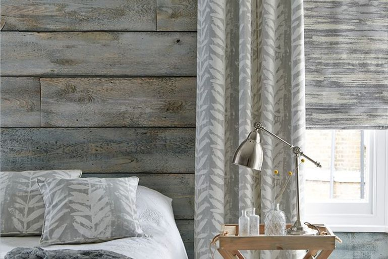 silver patterned roman blinds and curtains in a living room window