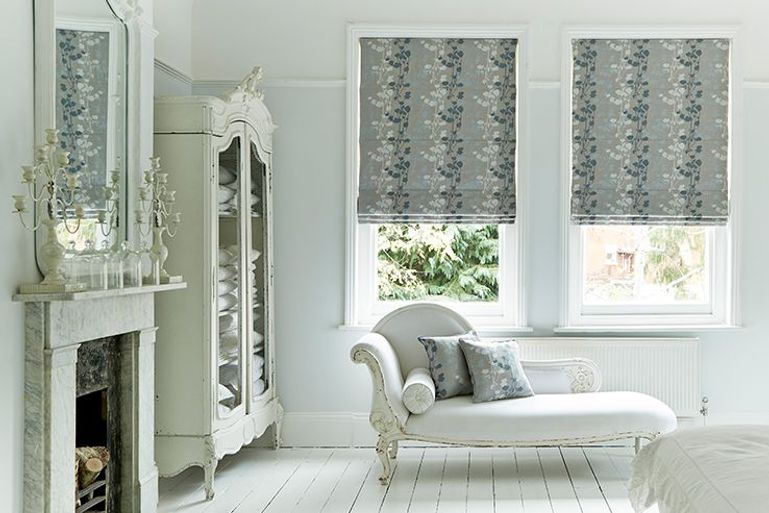 stylish silver blackout roller blinds with leafy pattern in a living room window