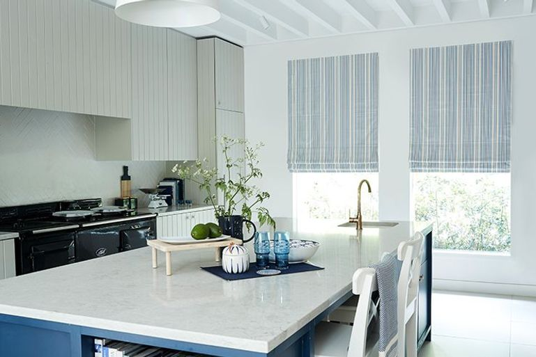 striped white and blue roman blinds in a blackout fabric hanging in a kitchen window