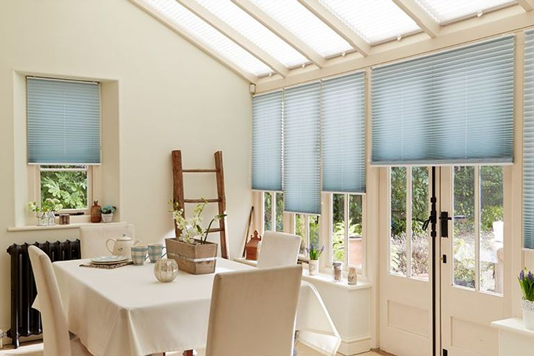 pleated blue blinds in a conservatory dining room window