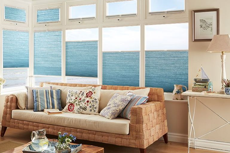 pleated blue blinds in a conservatory living room window
