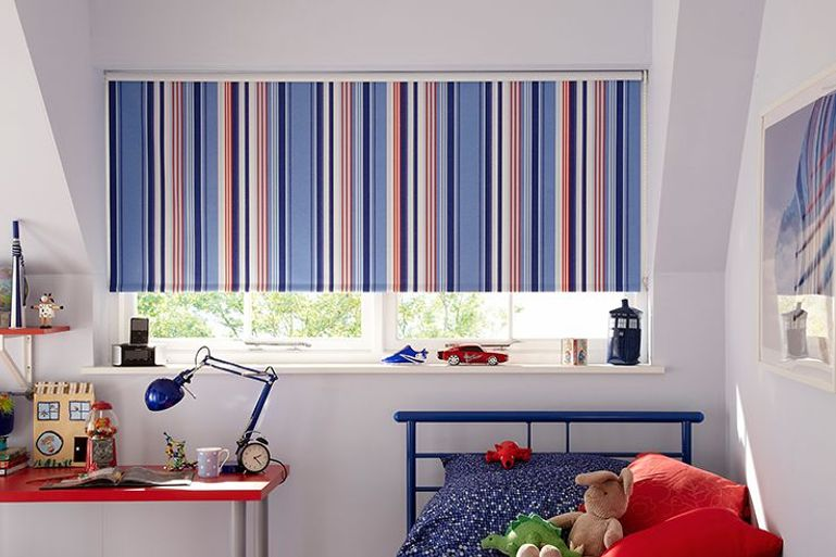 stripey blue roller blinds in a colourful bedroom window