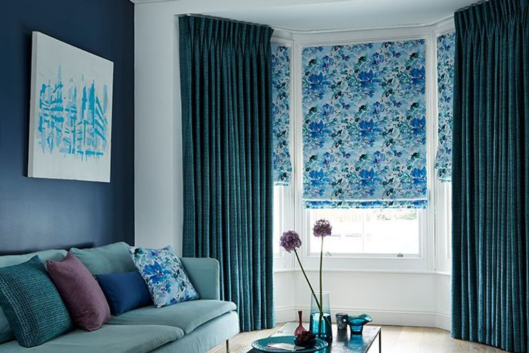 light blue patterned roman blinds with blue curtains in a living room