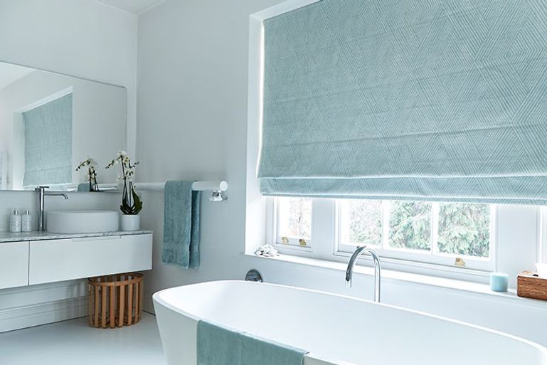 light teal blue roman blinds in a bathroom window