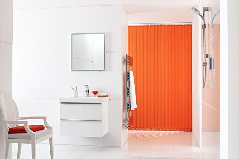 modern white bathroom with statement orange vertical blinds