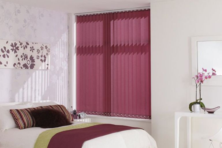 deep purple vertical blinds in a bedroom window