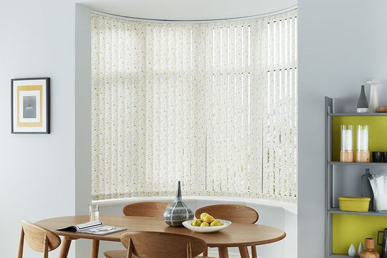 dining room with a bay window dressed with white vertical blinds