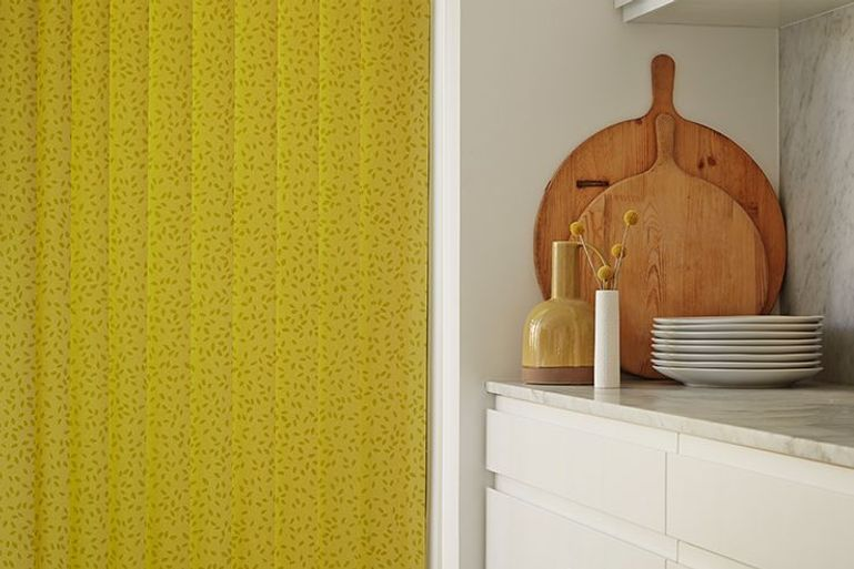 modern white kitchen counters next to statement yellow vertical blinds