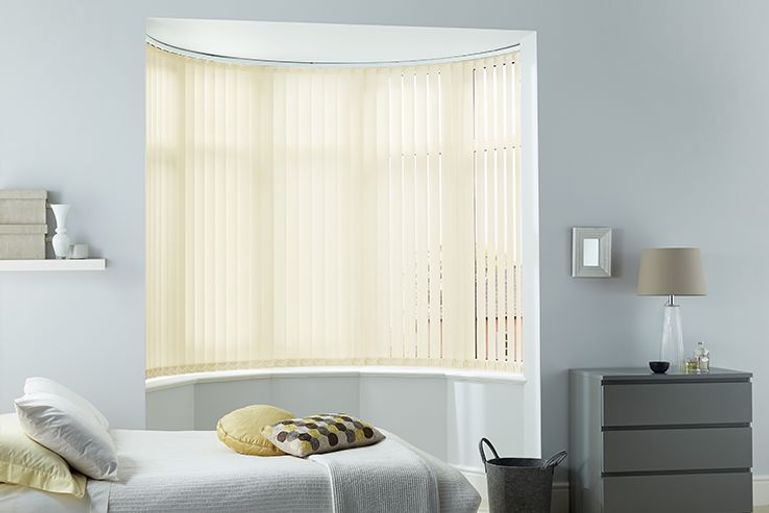 yellow vertical blinds in a bedroom bay window