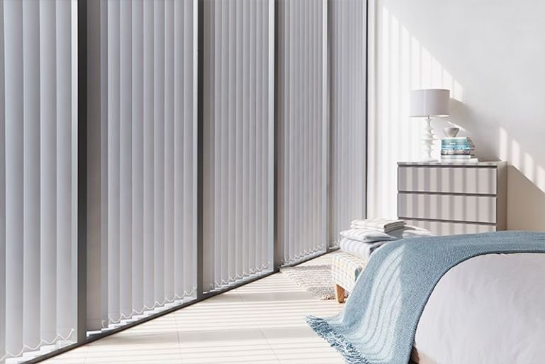 silver vertical blinds in a bedroom window