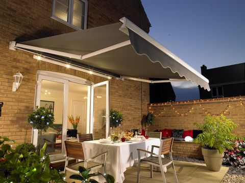 A grey awning hanging over a table set for dinner at nighttime, with fairy lights twinkling in the background
