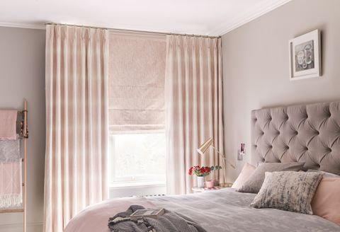 A bedroom featuring a bed in front of a window covered by a pink Roman blind under pink curtains