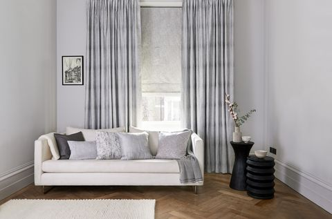Living room with white sofa covered in silver patterned curtains