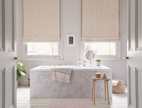Large bathroom with marble bathub in the centre of the room and two windows dressed with cream roman blinds