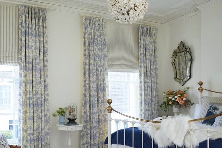 Toile French Blue curtains with Blue striped Roman blinds in a bedroom window