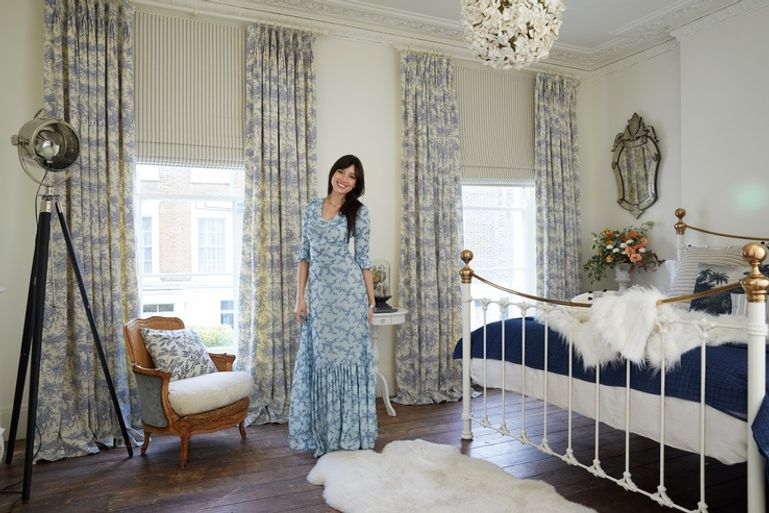 Daisy Lowe in a cosy country style bedroom with windows dressed with blue curtains in floral print