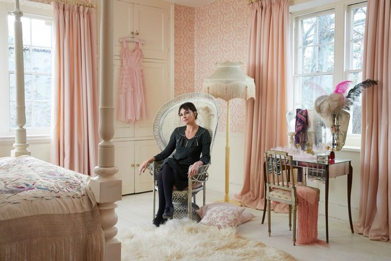 Women sat in an armchair in traditional bedroom with pink curtains