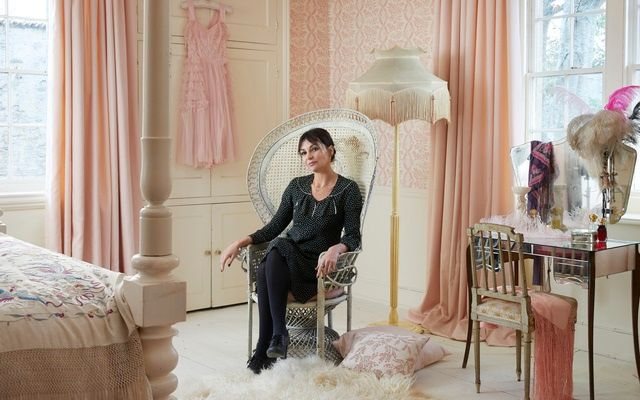 Peral lowe sat on a chair in bedroom. Room is decorated with pink curtains
